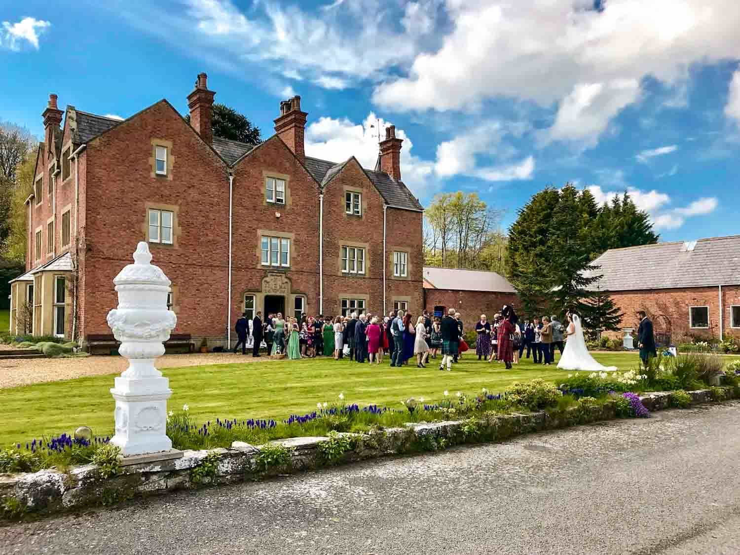 Wedding guests gather outside Henllan House