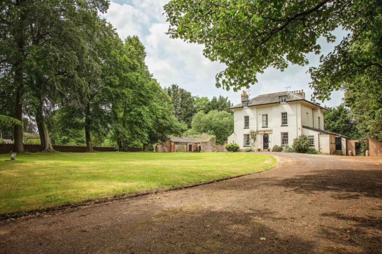 A grand manor house to rent with a long driveway