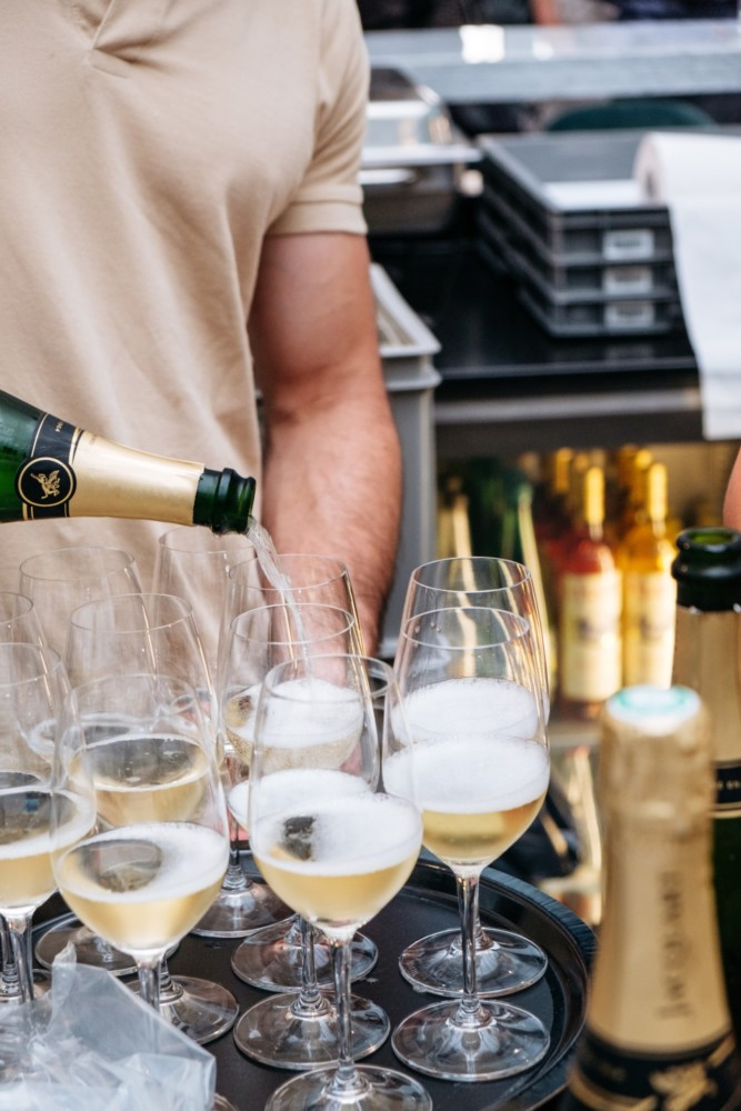 A bartender pours glasses of champagne